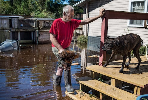 George Aubert rescues one of his chickens from rising floodwaters caused by remnants of Hurricane Matthew after it struck Fair Bluff, North Carolina, in 2016.