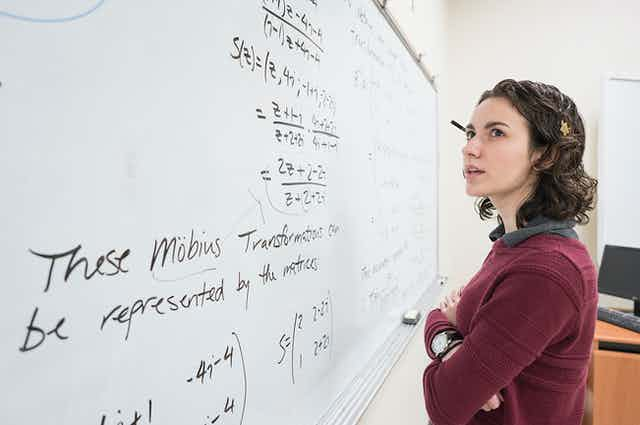a female college student looks at equations on a whiteboard