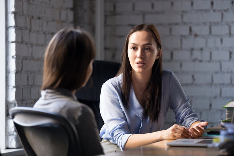 Woman consulting professional looking woman in office
