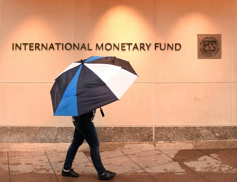 Person with umbrella walks past IMF building