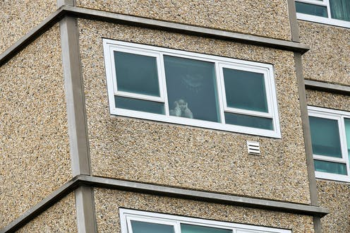 A child looks out of the window of a high-rise apartment under lockdown