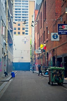 Rough sleeper packing up in Melbourne laneway