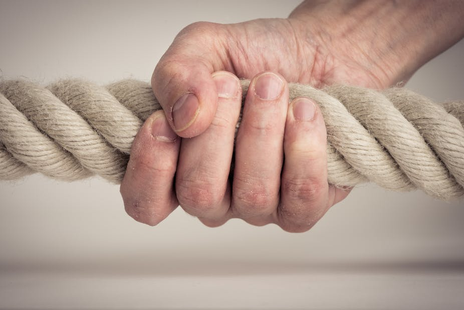 Person grips a rope tightly.