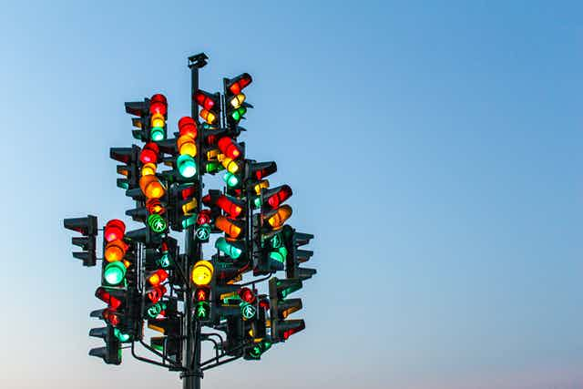 Multiple traffic lights all pointing in different directions.