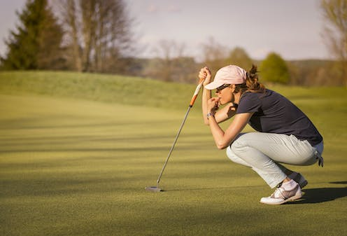 Golfer crouching down and concentrating on next putt.