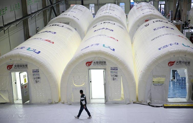 Un homme passe devant trois laboratoires pop-up gonflables.