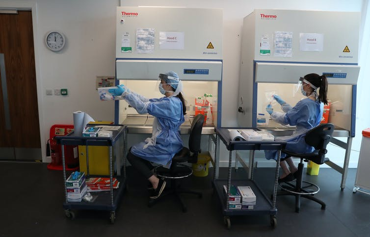 Deux femmes portant des EPI analysent des échantillons dans un laboratoire.