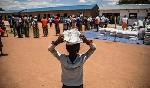An African child balances a package on his head, with adults standing nearby alongside sacks of food.