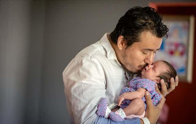 A man kissing his newborn daughter.