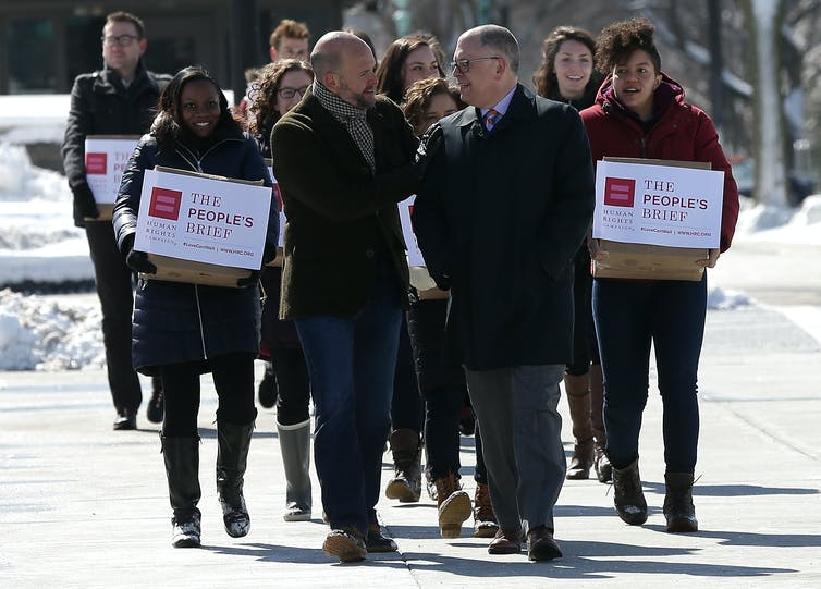 Group of people carrying boxes with the amicus brief to the Supreme Court.