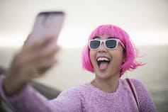 Mujer joven con cabello rosado tomando un selfie