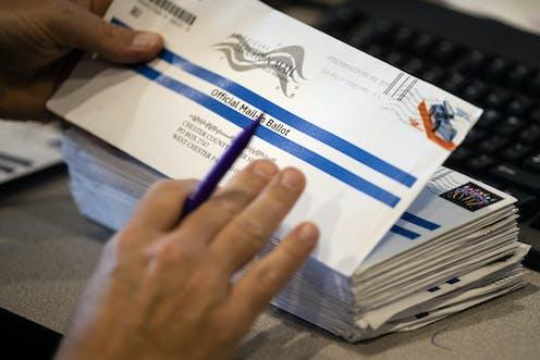 A person handles a mailed ballot