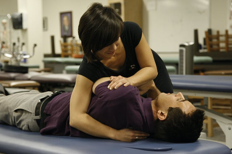 woman manipulating a man lying on a treatment table