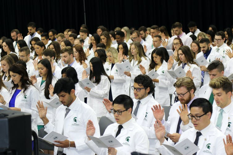 crowd of D.O. students wearing their white coats