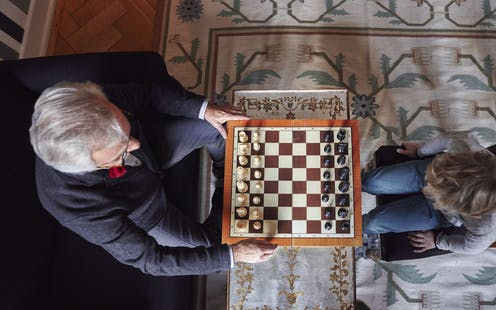 An elderly man plays chess with a child.