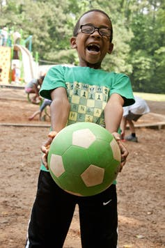A Black boy wearing glasses in a green T-shirt laughing and holding a green and while soccer ball.