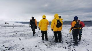 Seis turistas parados sobre hielo de espaldas a la cámara