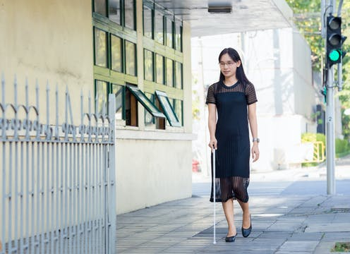 A young woman with impaired vision wearing a black dress, walking on the sidewalk with a white cane.