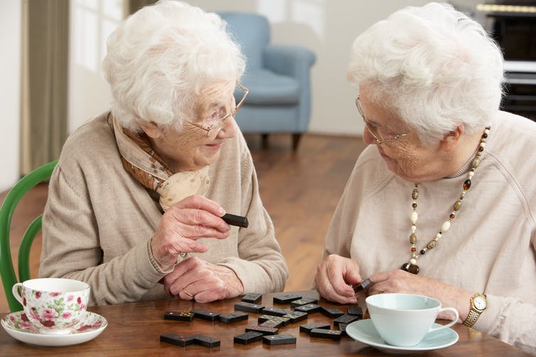 Two elderly women playing with dominoes.