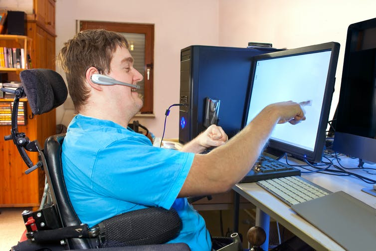 A young man with cerebral palsy in a wheelchair wearing a blue T-shirt and using a computer and a headset.