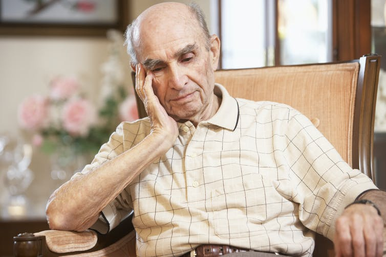 An elderly man, looking despondent, sits in a chair.