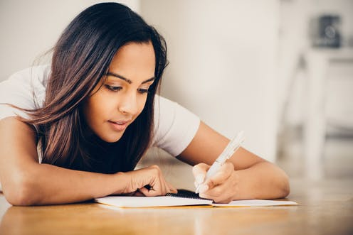 A teenage girl writing in notebook