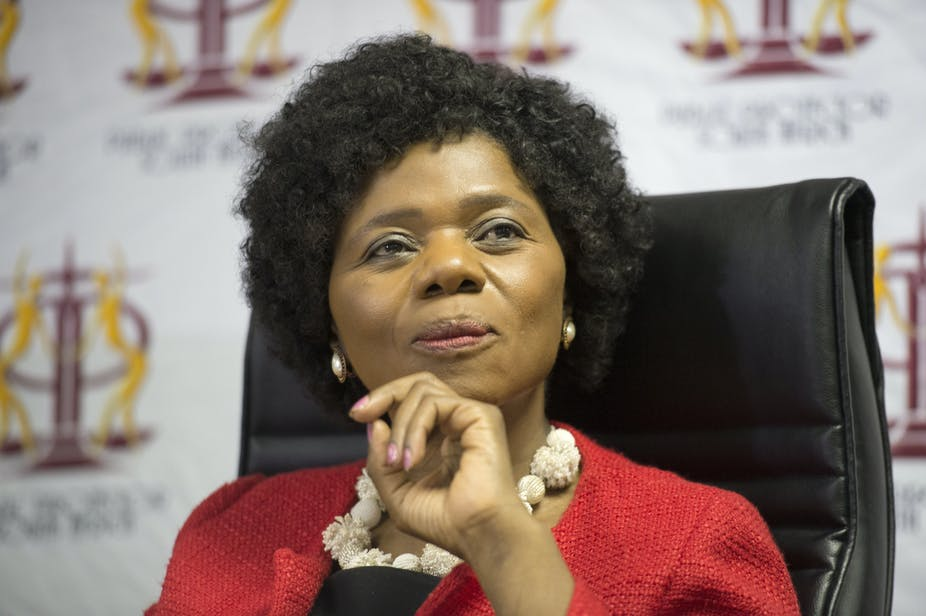 Thuli Madonsela, wearing a black afro wig and red jacket in deep thought behind a desk.