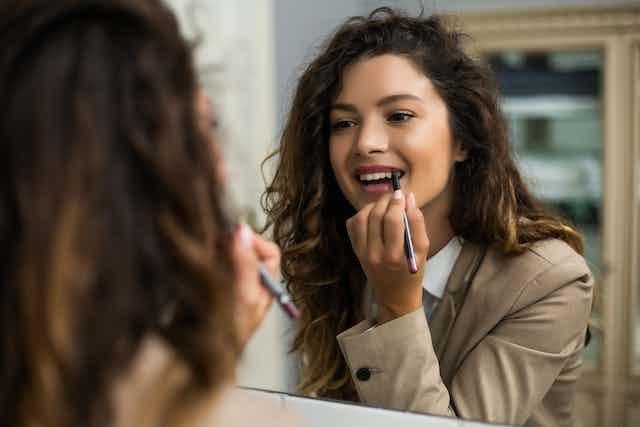 Office woman applying lipstick at mirror