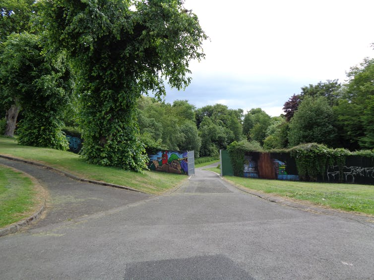 Park landscape with wall and opening in it for a path to go through