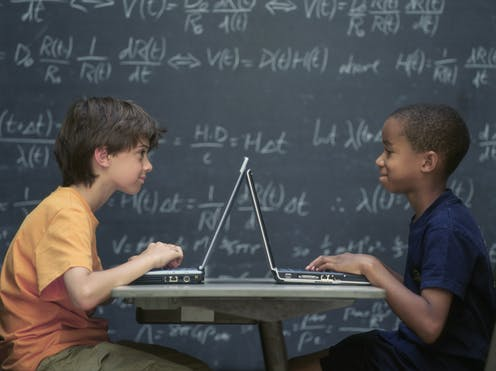 Two boys sitting at desk with laptops in front of then and a blackboard in the background with maths equations.