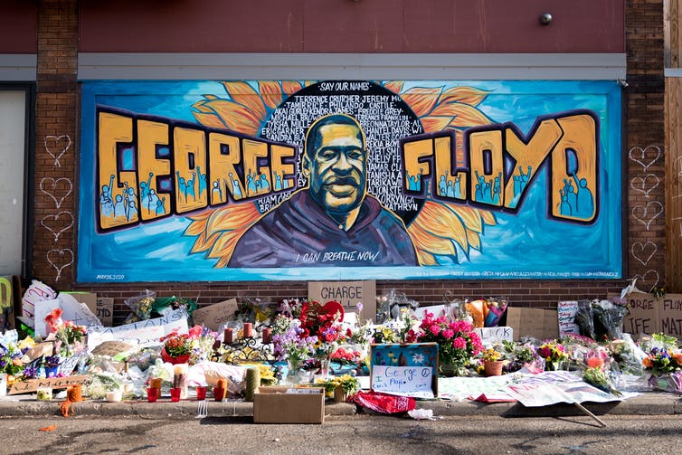 Mural on wall of George Floyd with flowers and cards in front.