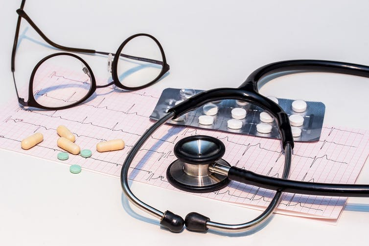 An ECG printout, stethoscope, eyeglasses and medication.