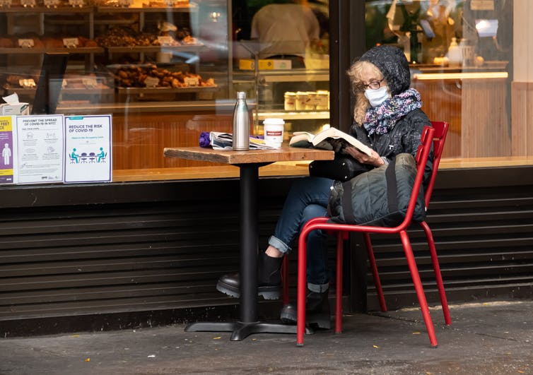 A woman in face mask and jacket sits outside a bakery.