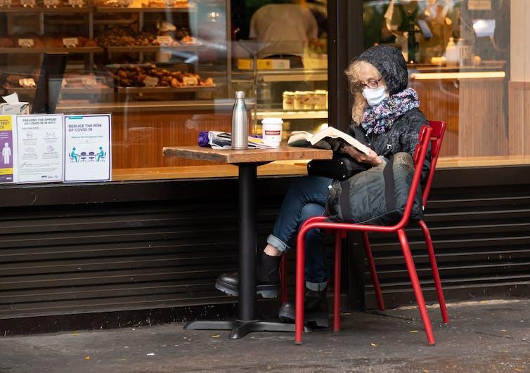 امرأة ترتدي قناعاً وسترة تجلس خارج مخبز.