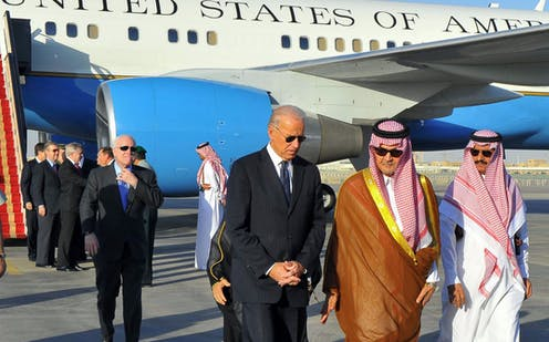 Biden walks with two Saudi men at an airport, with Air Force Two visible in the background