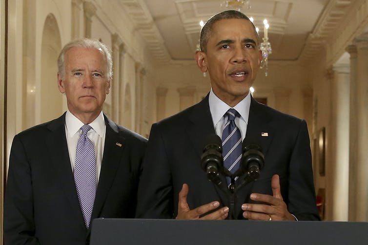 Obama speaks at a lectern with Biden behind his right shoulder