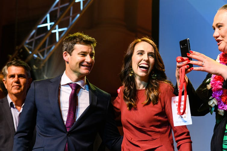 Jacinda Ardern and her fiance Clarke Gayford, smiling on stage