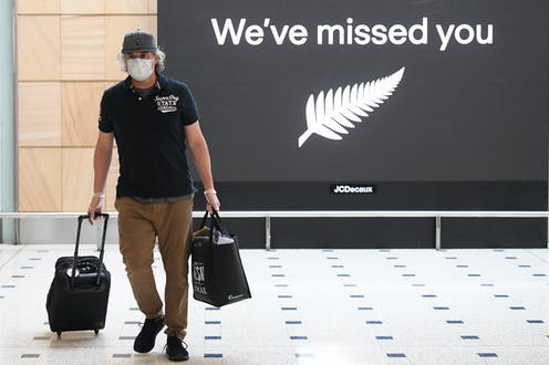 """A man, at Sydney airport, walks passed a sign saying """"We've missed you"""" with the New Zealand silver fern"""