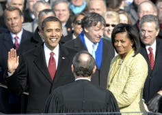 Obama smiles with his right hand raised as he takes the oath of office at his inauguration.
