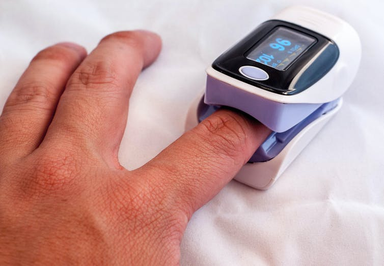 A person with a pulse oximeter on their finger, measuring their blood oxygen levels