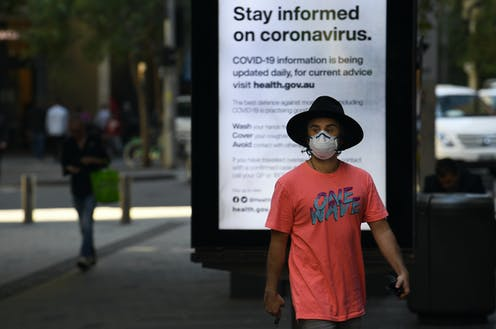 """A man wearing a hat and facemask walks in front of a sign reading """"Stay informed on coronavirus""""."""