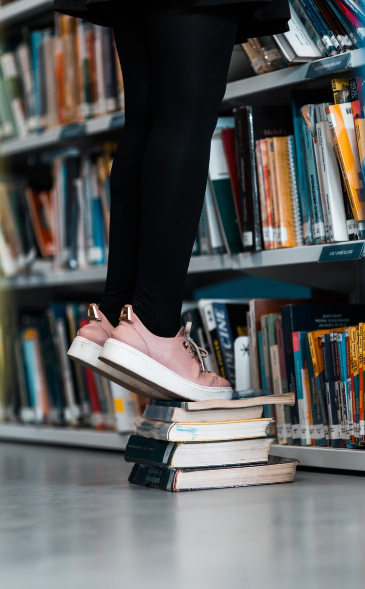 Girl uses stands on a stack of books