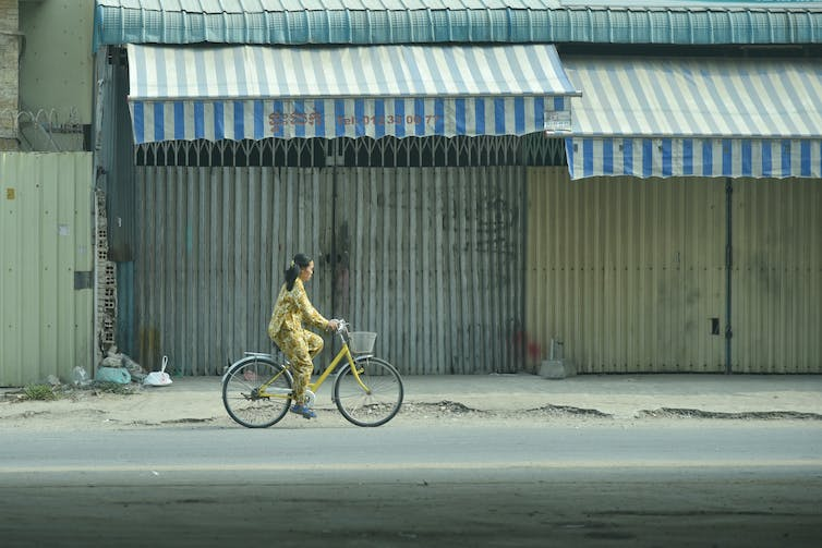Woman rides a bicycle through Phnom Penh