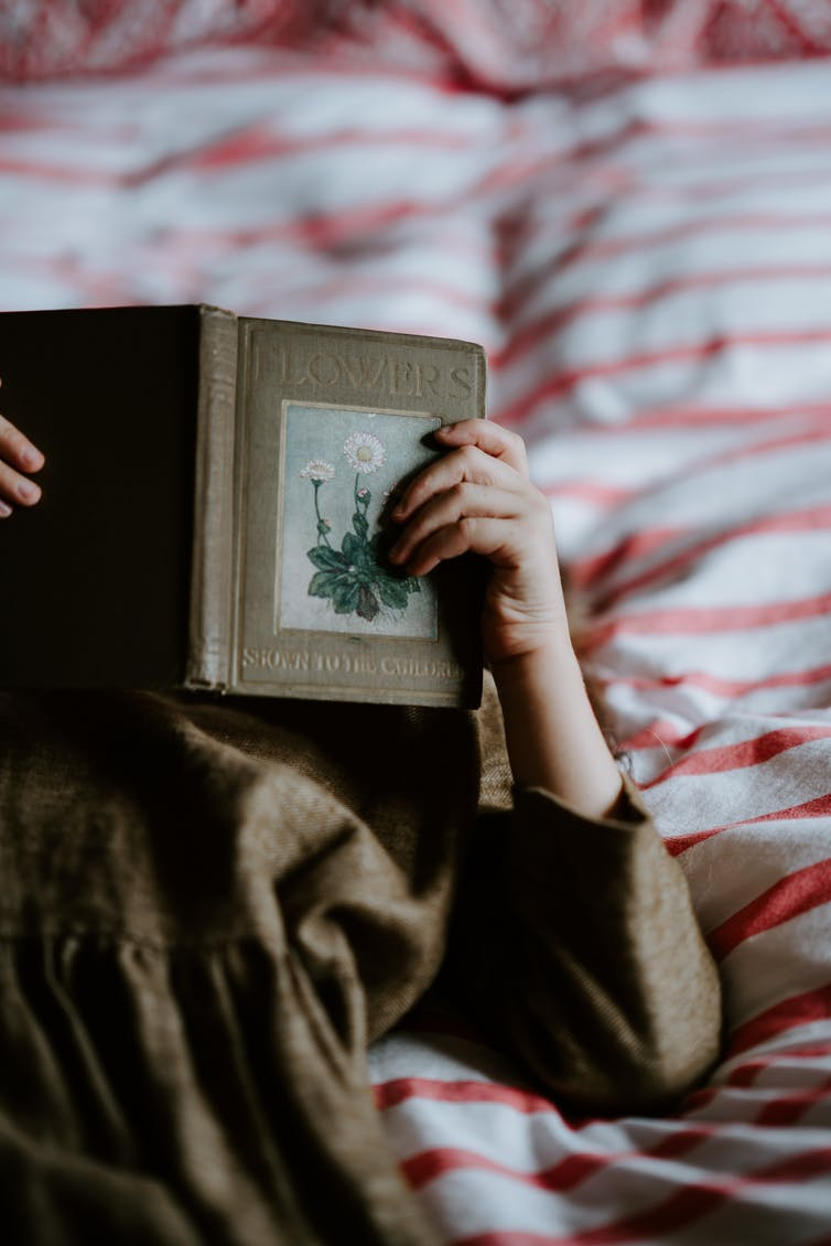 Girl reads a book in bed