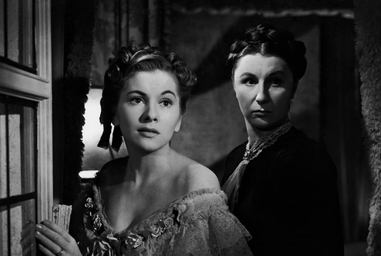 Older woman and younger woman look in mirror, scene for black and white film.
