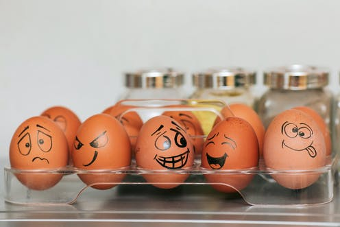 A box of eggs with emotional faces drawn on.