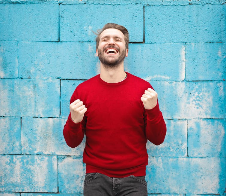 A grinning man in red jumper stands in front of blue wall.