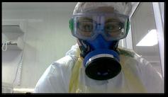 Un chercheur porte des lunettes, un respirateur et des vêtements de protection à l'intérieur d'un laboratoire.
