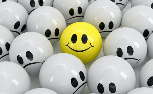 A yellow ball with a smiley face among several grey balls with frowny faces