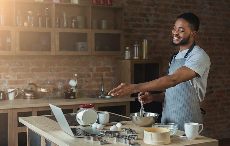 Man making cake points at open laptop.